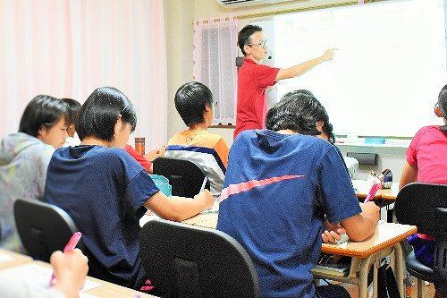 中学生少人数クラスの授業中の生徒と塾長